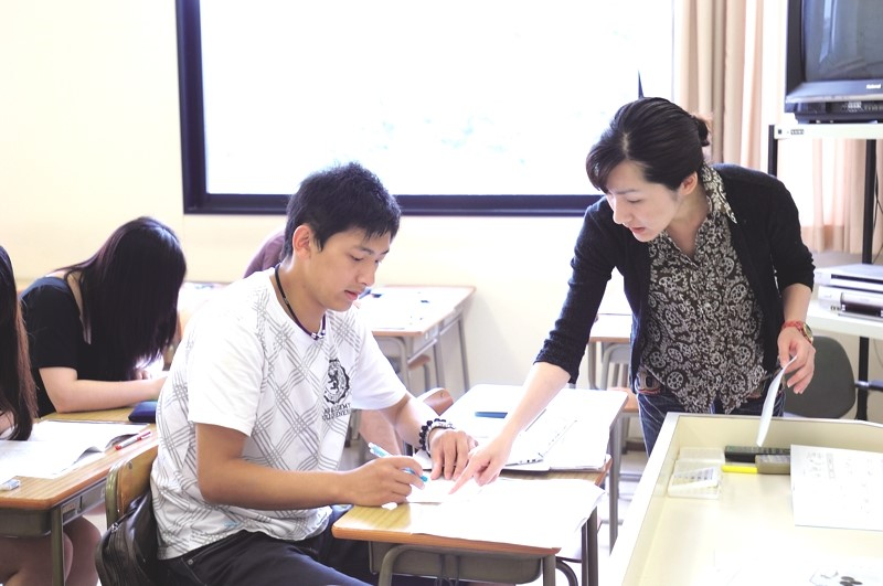 Lecturer Nozomi Tamaki gives a suggestion during a written expression class.