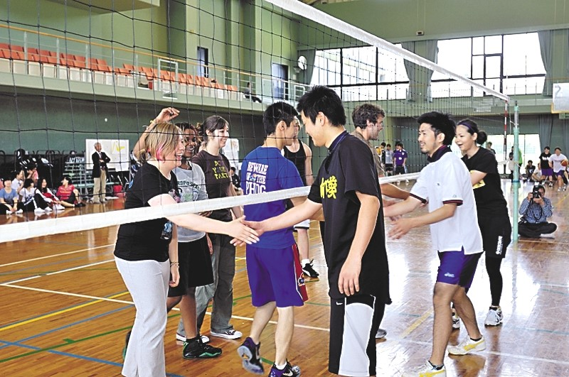 Students shake hands at the end of the university volleyball tournament.