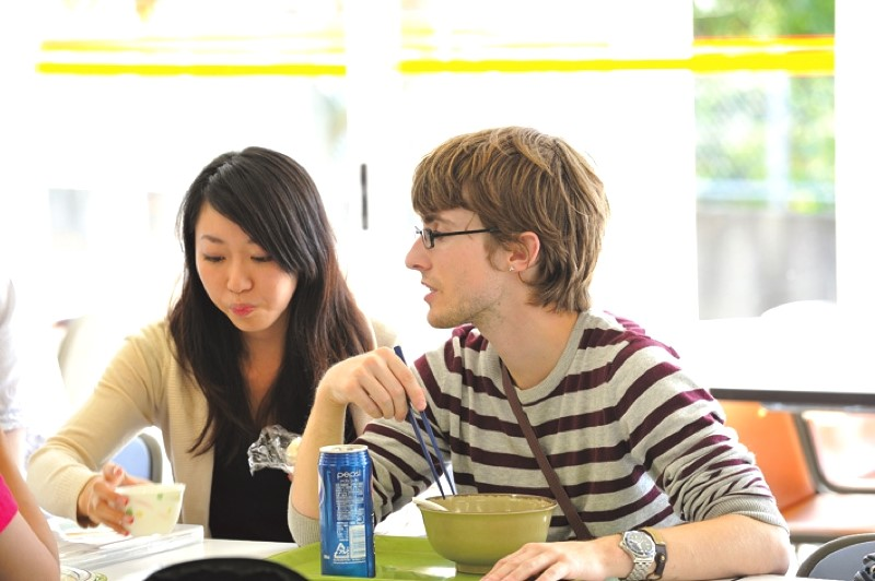 Two students eat and study at the French-speaking table.