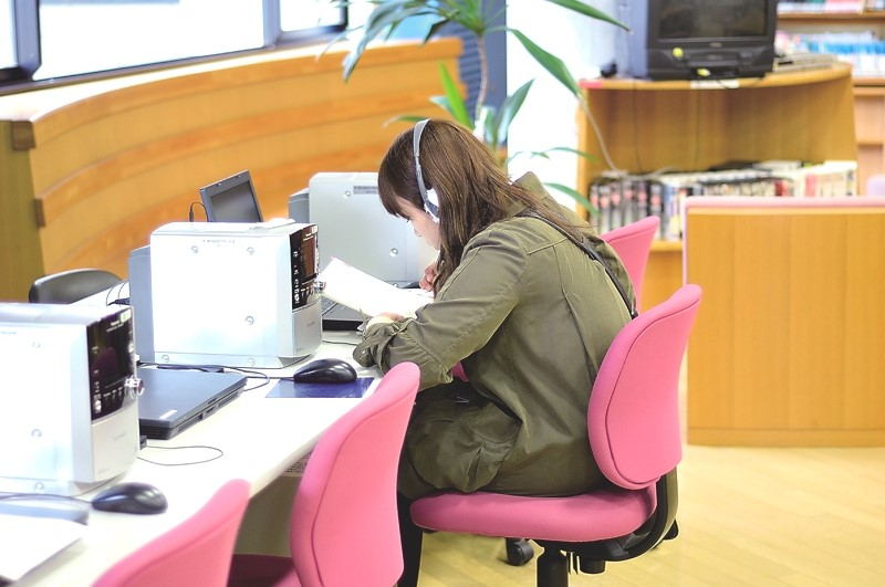 A student prepares for class with audio equipment in the library.