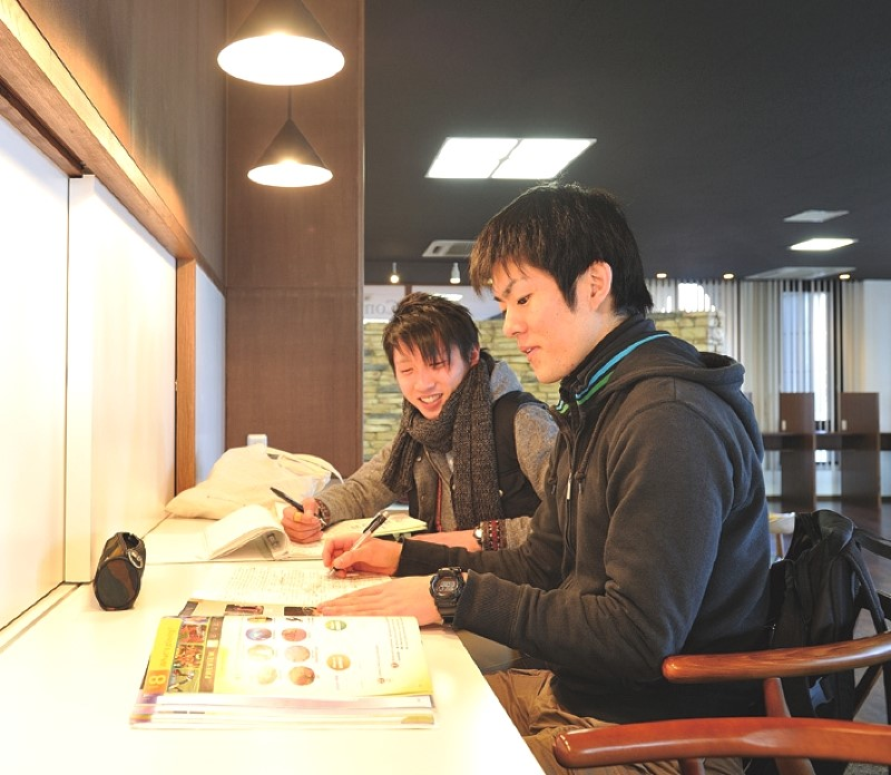 Two students study English in the lounge.