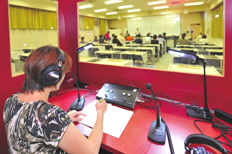 A student practices with the simultaneous interpretation equipment in the Media Center.