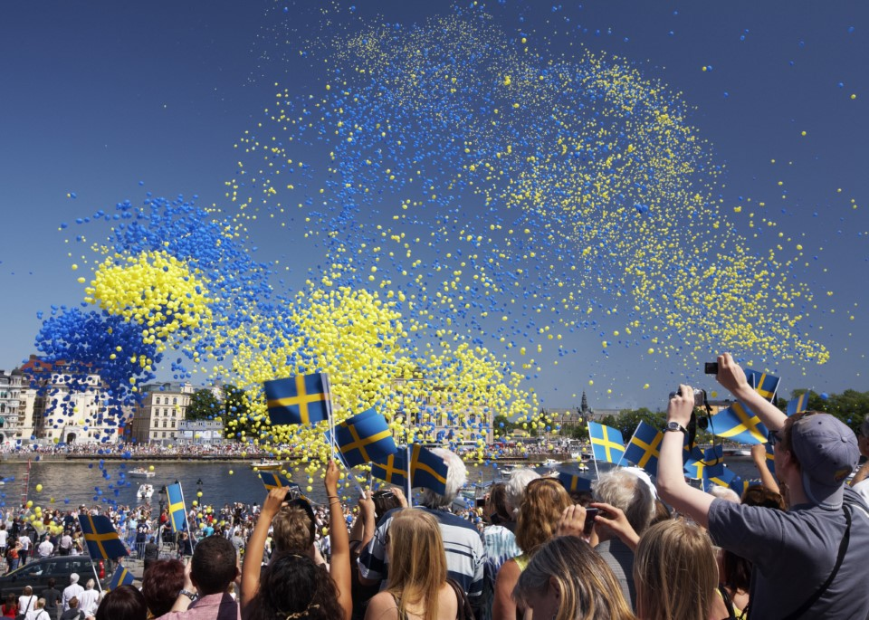 Every year, the King and Queen of Sweden celebrate National Day by taking part in a ceremony in Stockholm, where the yellow and blue Swedish flag is run up a mast. Children in traditional peasant costumes present the royal couple with bouquets of summer flowers.