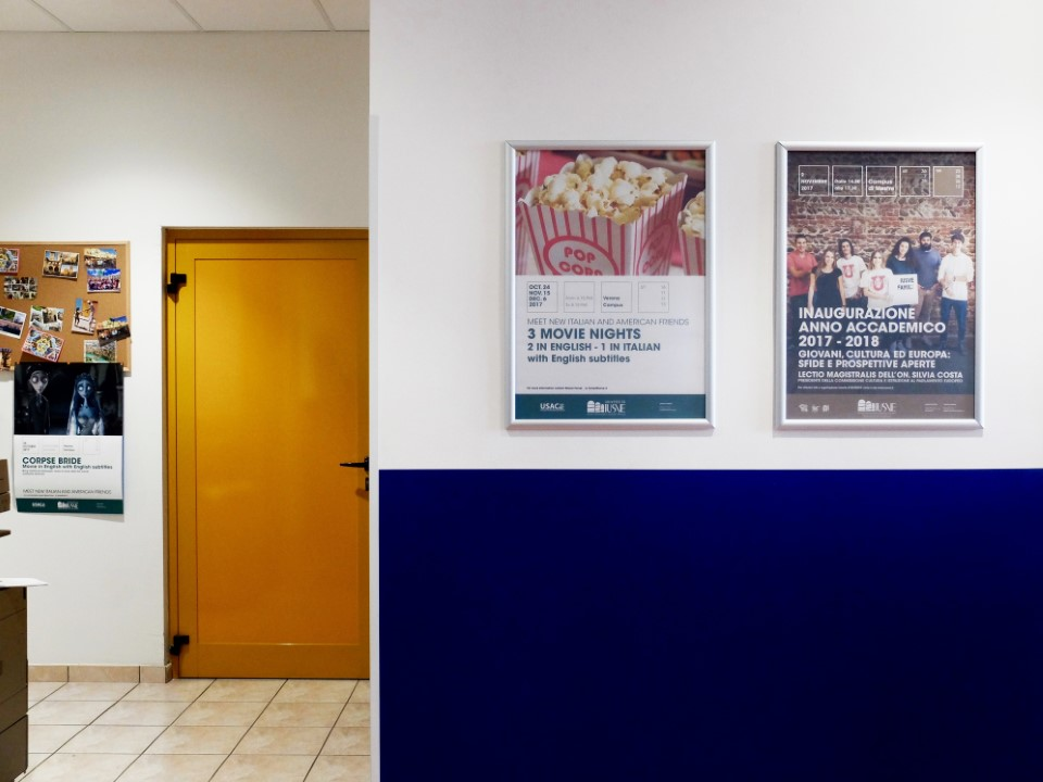 USAC posters hang on the wall on the blue floor at IUSVE University.