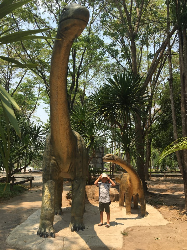 A local child plays next to a dinosaur statue in Khon Kaen.