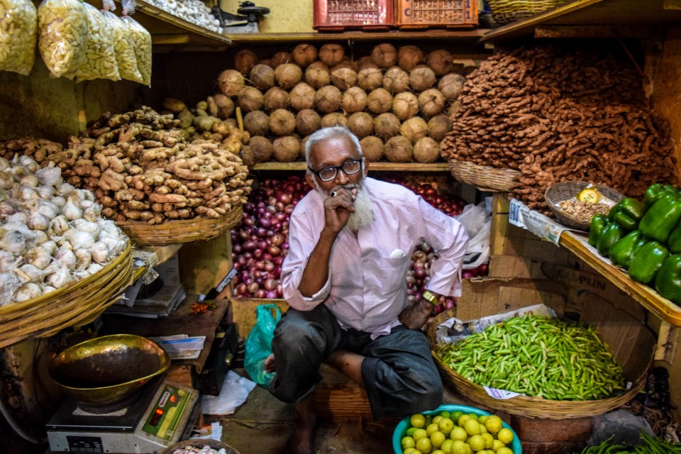 This photo portrays an older man selling a variety of fruits and vegetables, before I took this I asked if I could take his picture and he nodded and took on this pose.